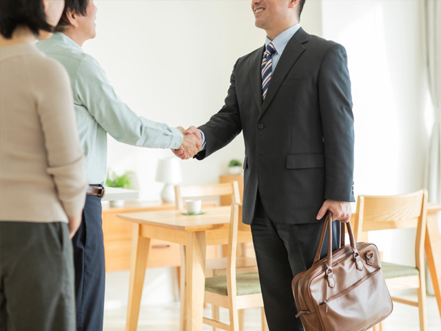 男性を握手する不動産スタッフ